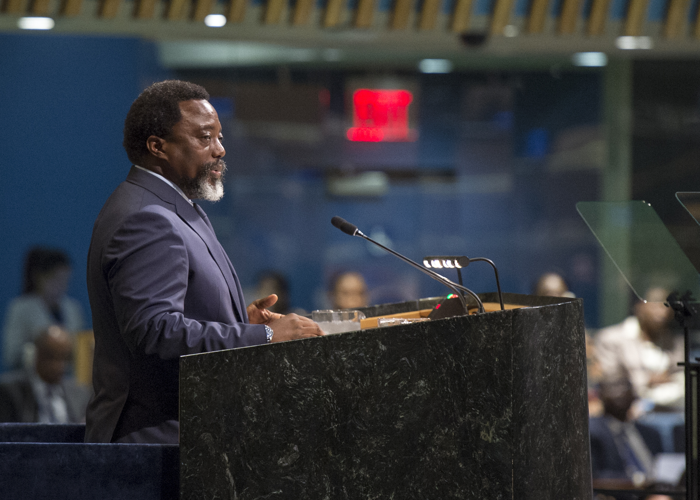 Joseph Kabila Kabange, President of the Democratic Republic of the Congo, stands in profile at a podium