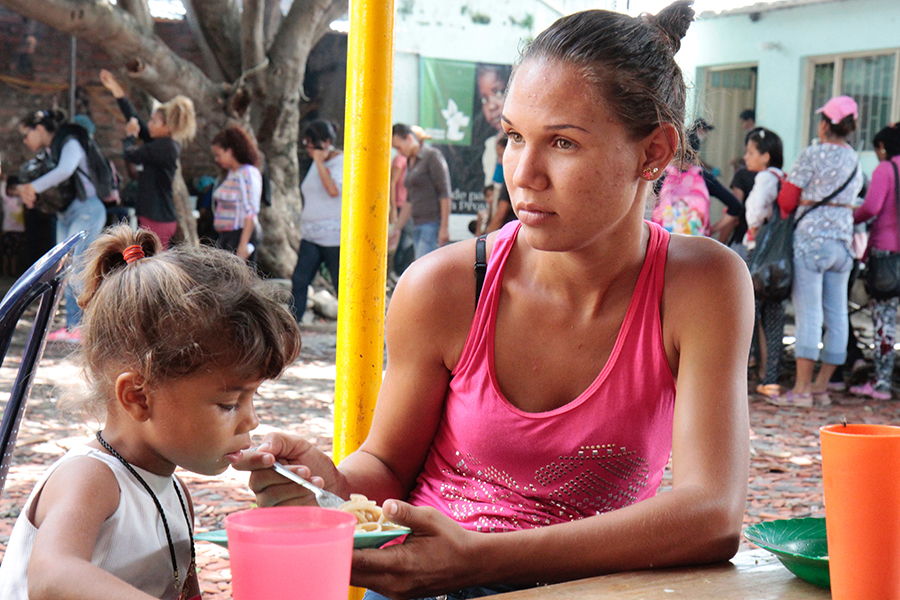 A Venezuelan migrant feeds her child