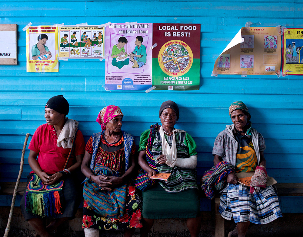 Four women sit on a bench in front of a blue wall while they await treatment in outside the Surgical Ward at Tari Hospital in Papua New Guinea's Hela Province