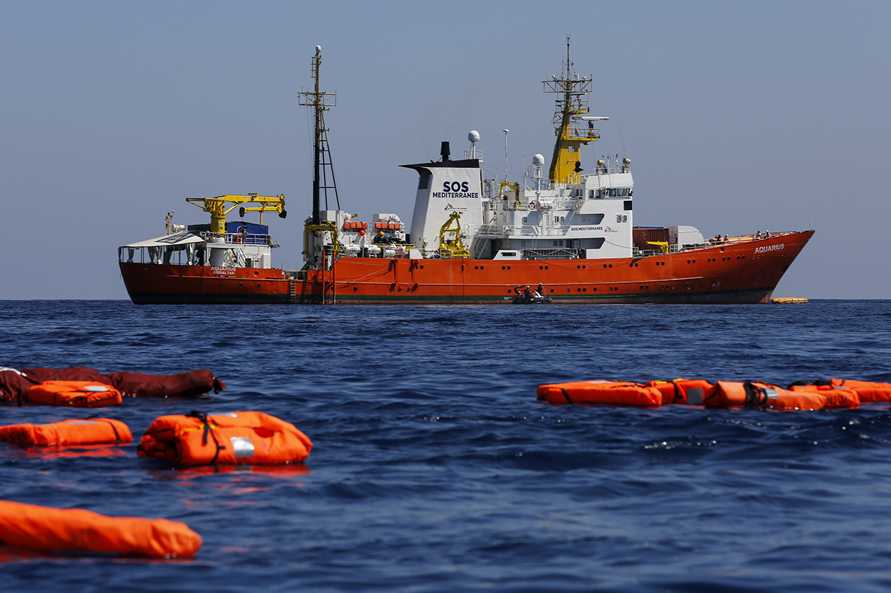 Orange life jackets floating in the sea mirror the Aquarius rescue vessel in the background