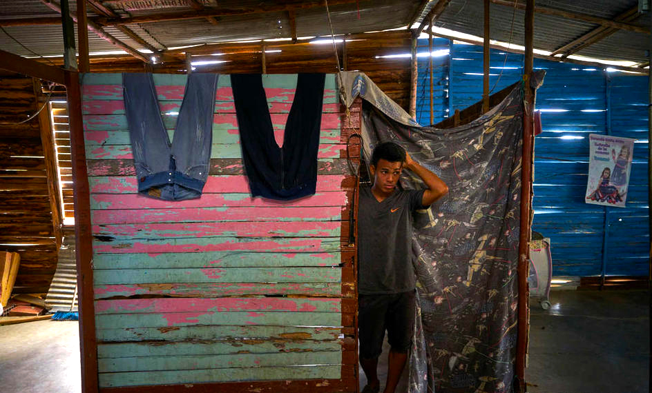 A man stands in a makeshift shelter with light pouring in from gaps in slats