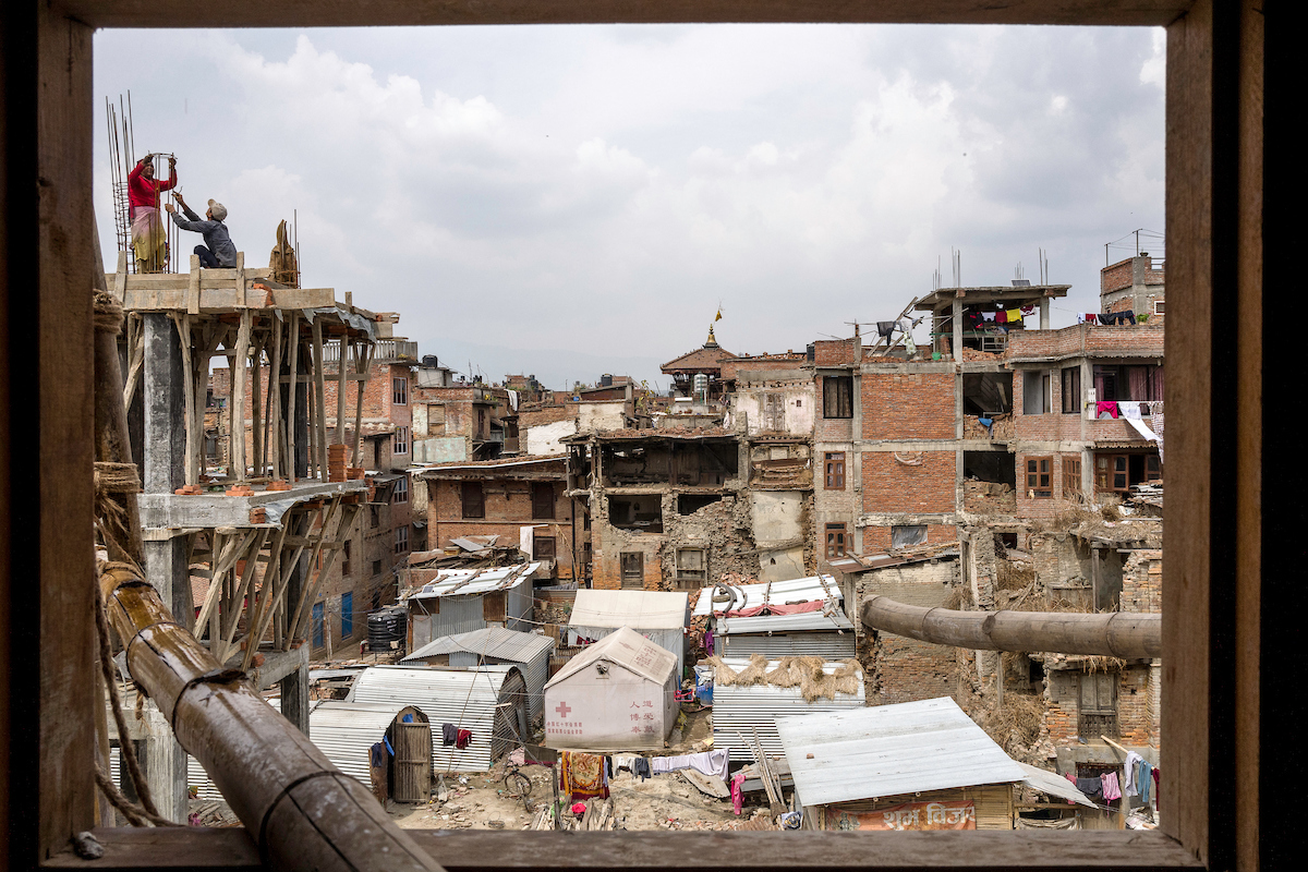 Workers are seen through the window of a building in construction in a square in Bhaktapur, Nepal