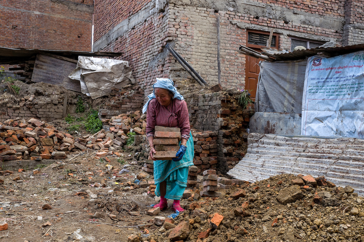 Kie Sari collects bricks that she salvaged from her destroyed home in Harisiddhi. Kie, 74, is a widow and has no one to help her, and she has not received help from the government. She spends her days collecting bricks that she cleans and piles up to be r