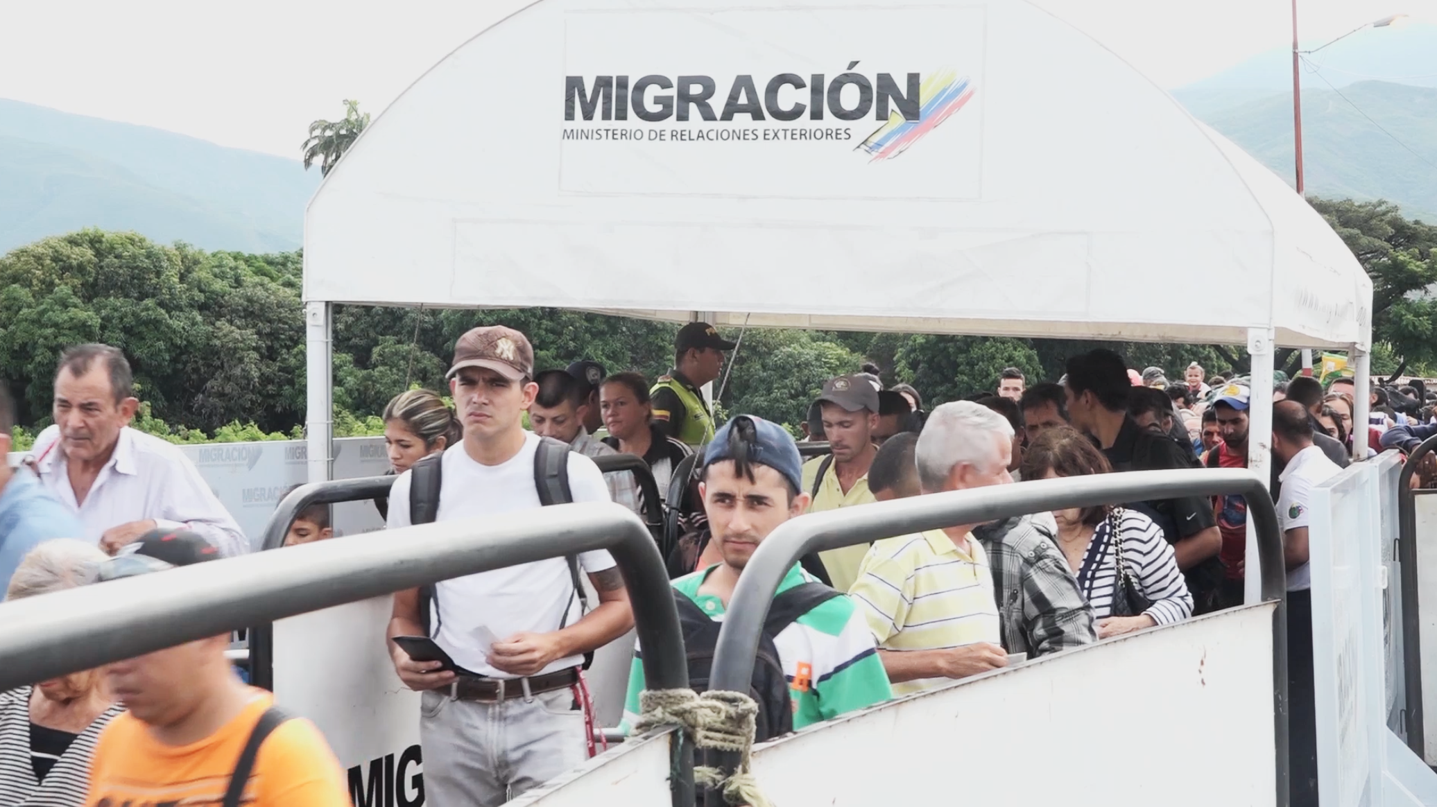 Venezuelans cross the border into Colombia under a sign that reads \