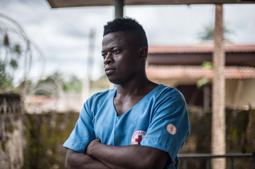 A portrait of a burial worker in Sierra Leone dressed in blue scrubs.