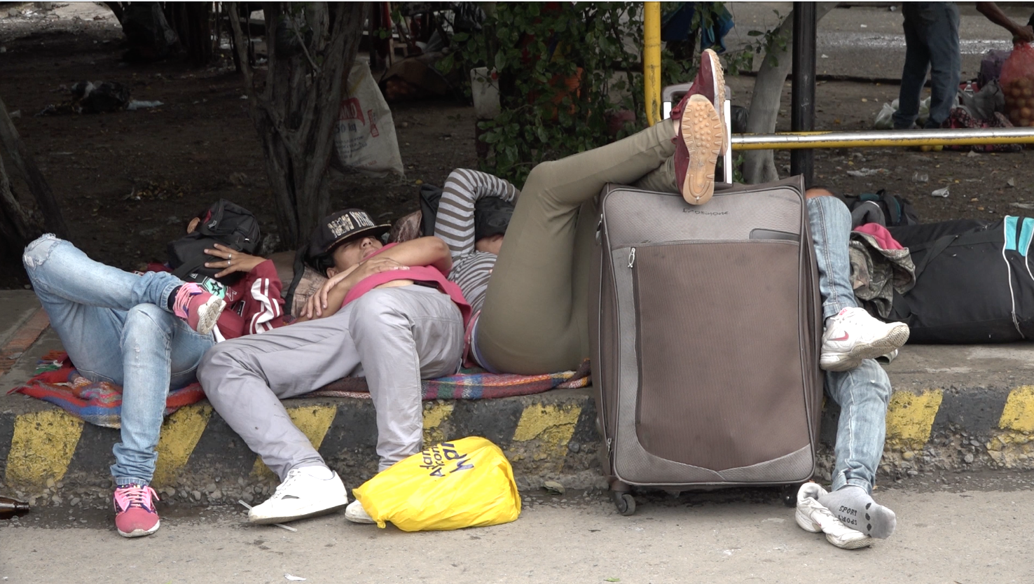 People asleep on the street with suitcases in Colombia