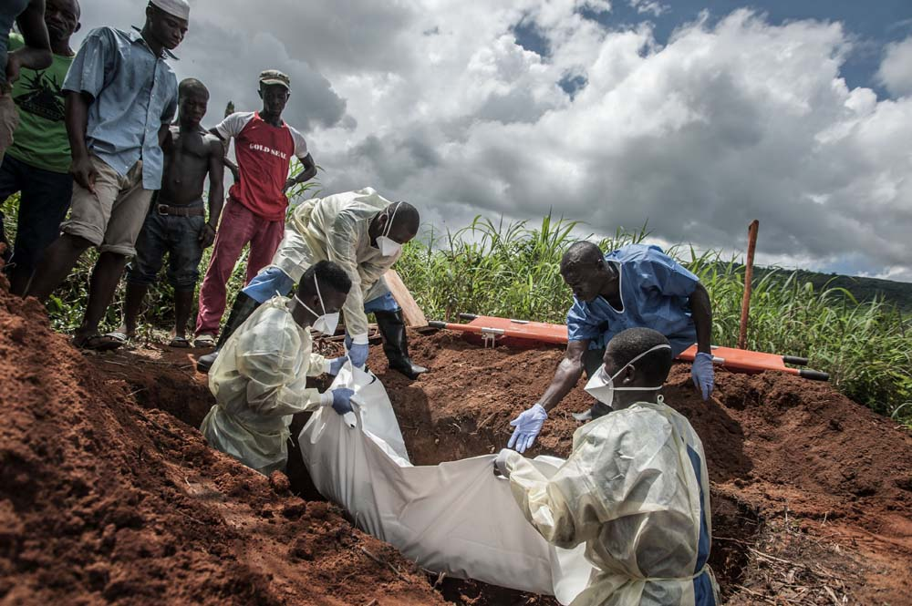 A group of burial workers in protective gear lower a covered body into a grave as onlookers stand by.