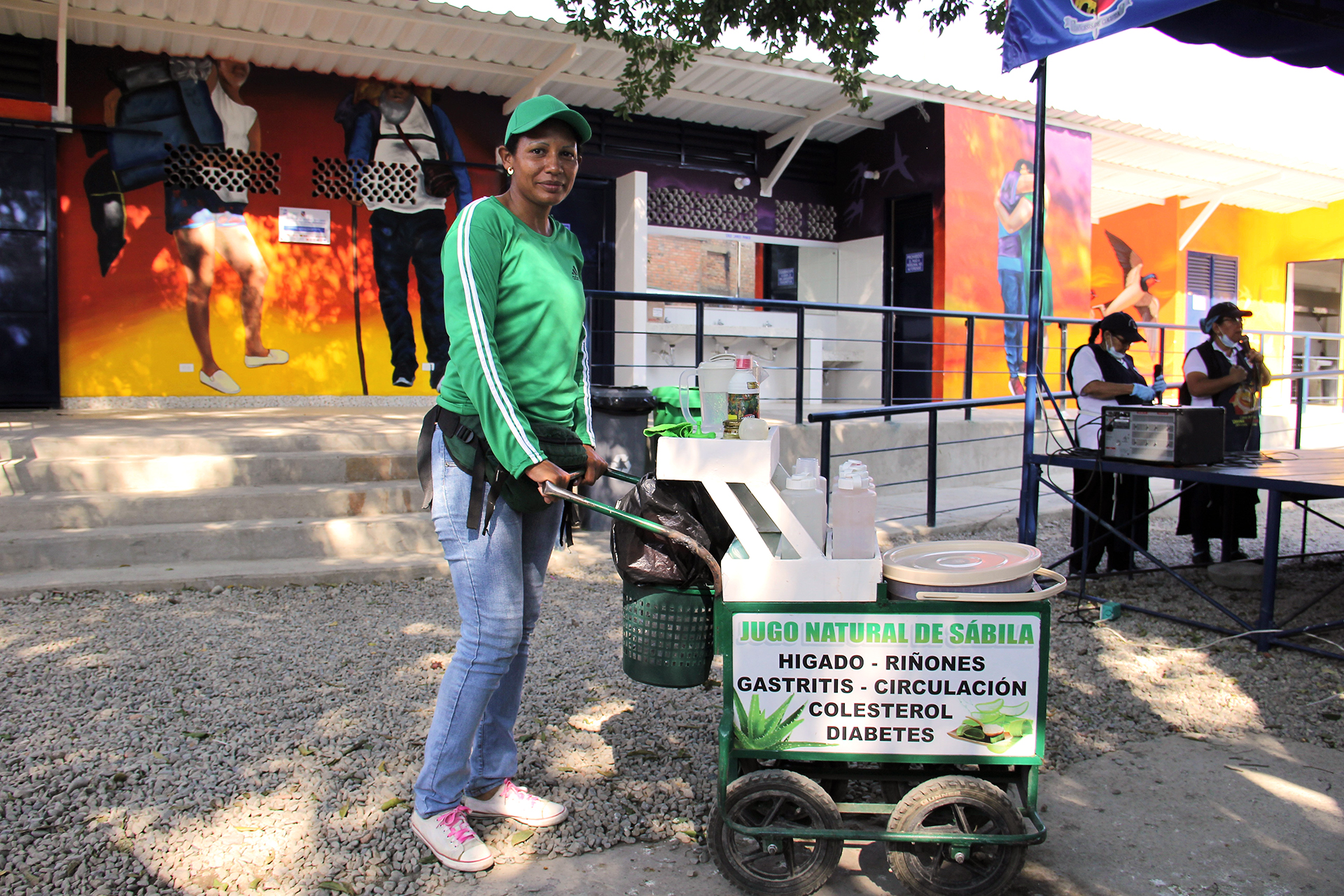 A woman stands in the shade with her cart selling Aloe Vera juice