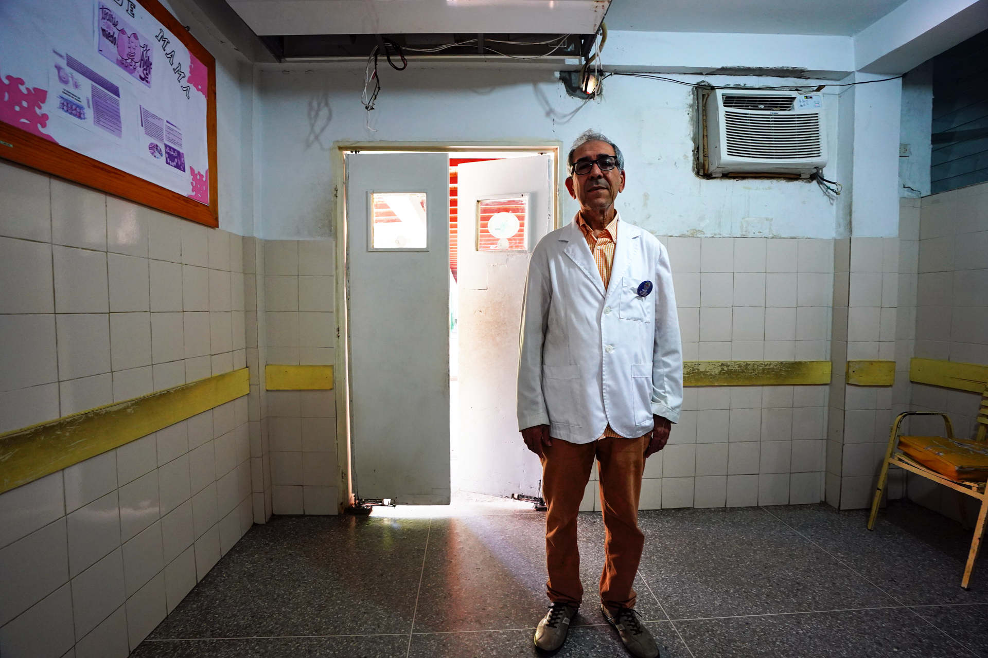 A wide shot of a doctor in a side room of a hospital
