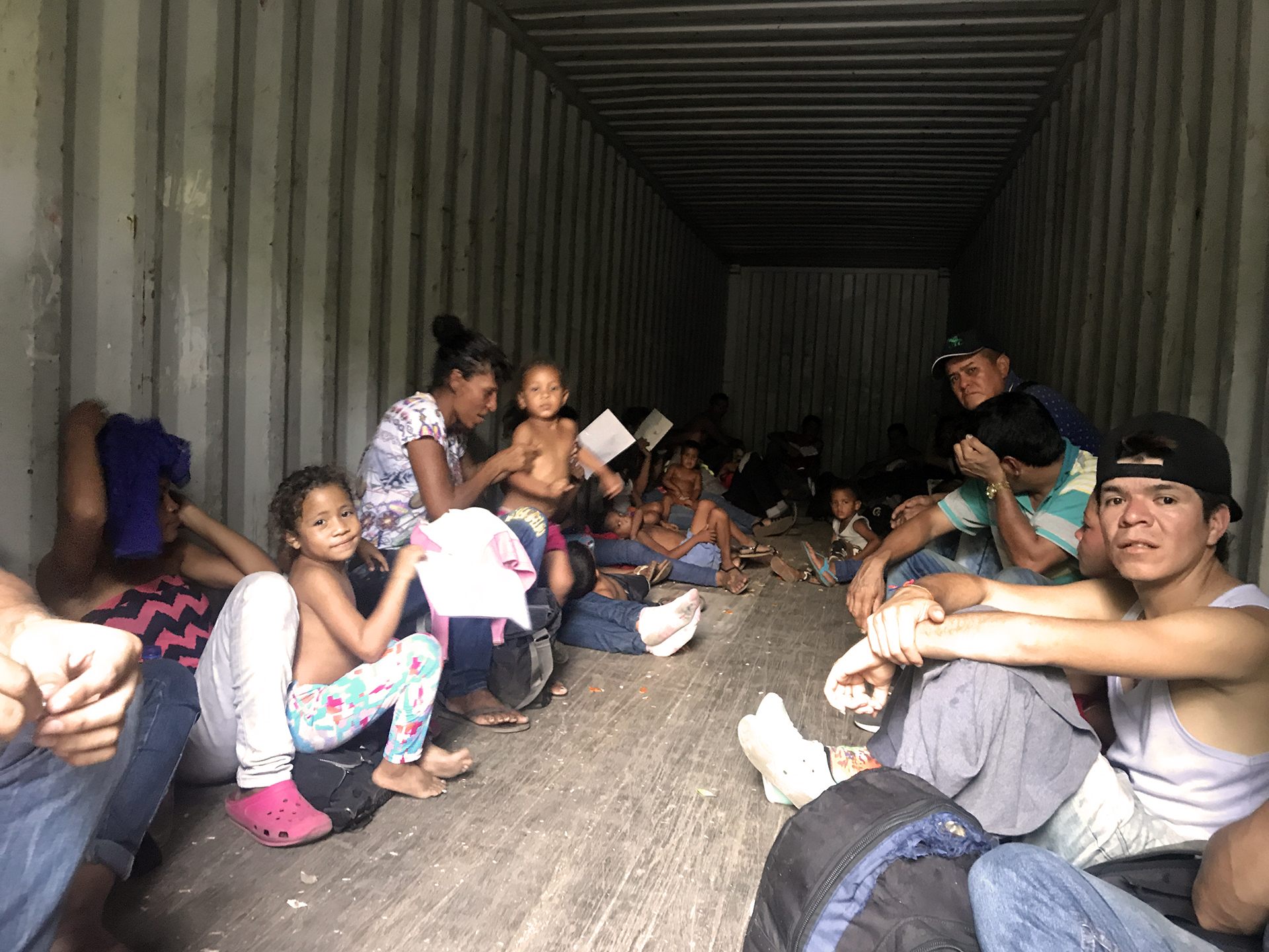 A group of men, women, and children in the back of a shipping lorry