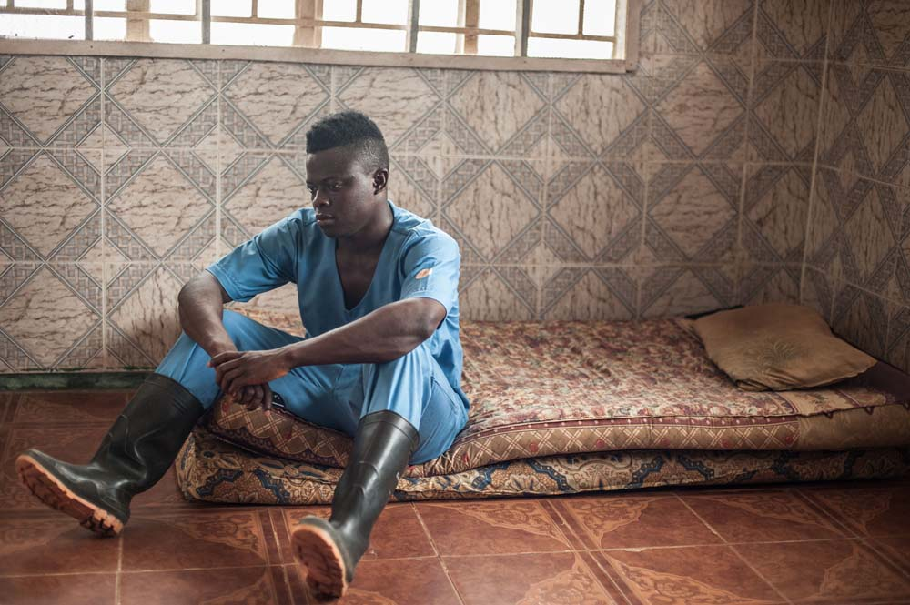 Tamba Momorie, an ebola burial worker in Sierra Leone, sits on a mattress on the floor in his scrubs.