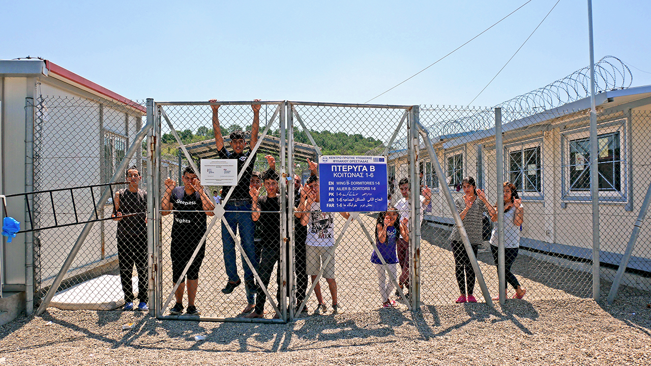 A group of Syrian and Iraqi refugees behind a fence