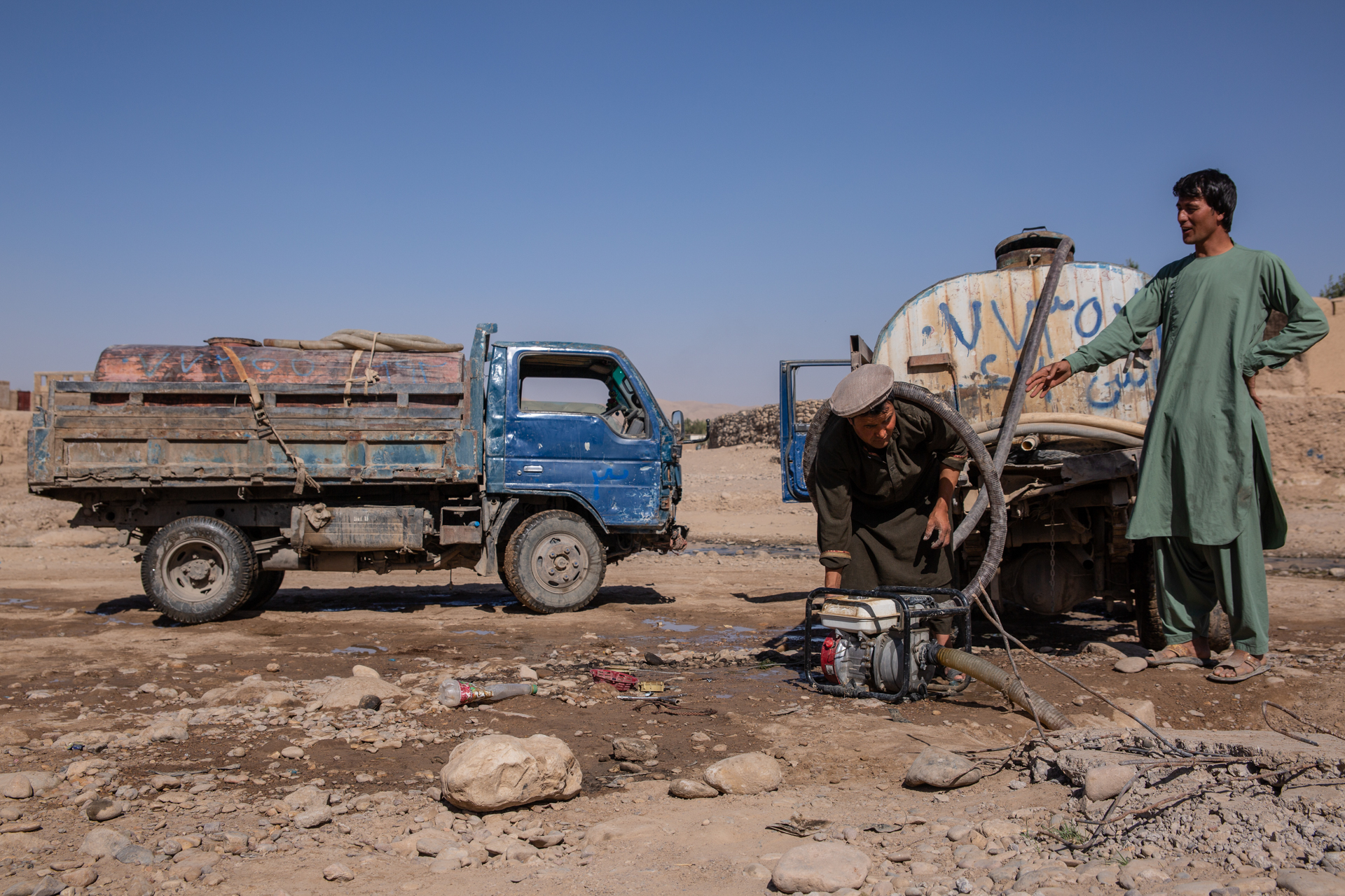 Two men in Afghanistan with trucks and a water pump in the dirt