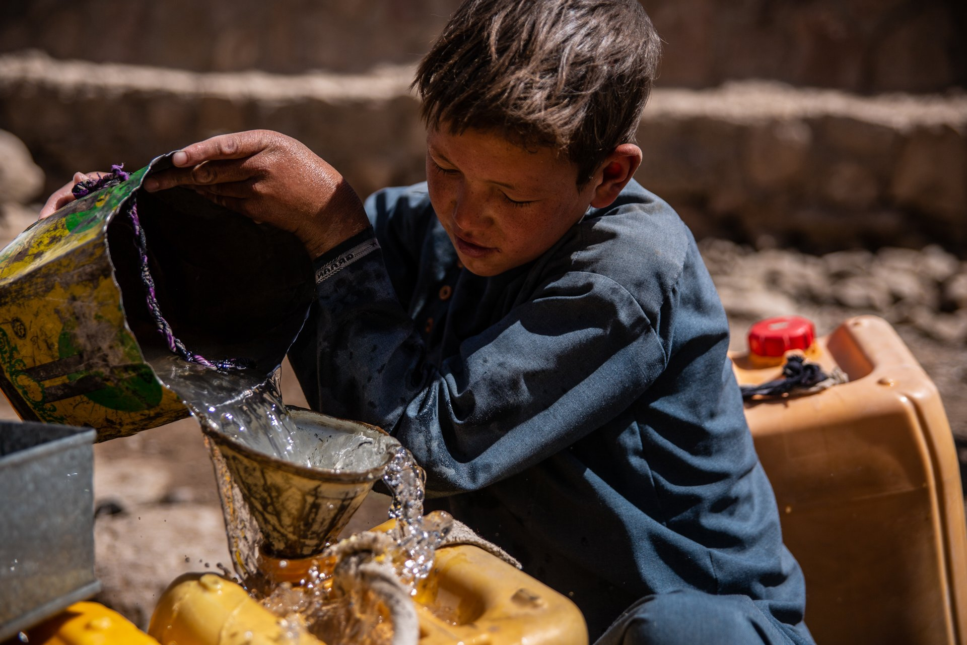 A young boy in Afghanistan pours water