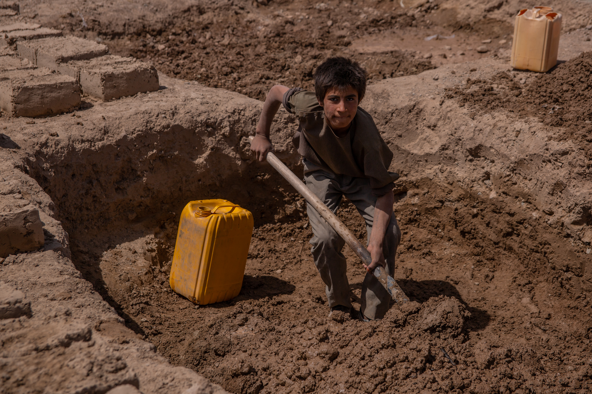 A young person shovels mud for a structure