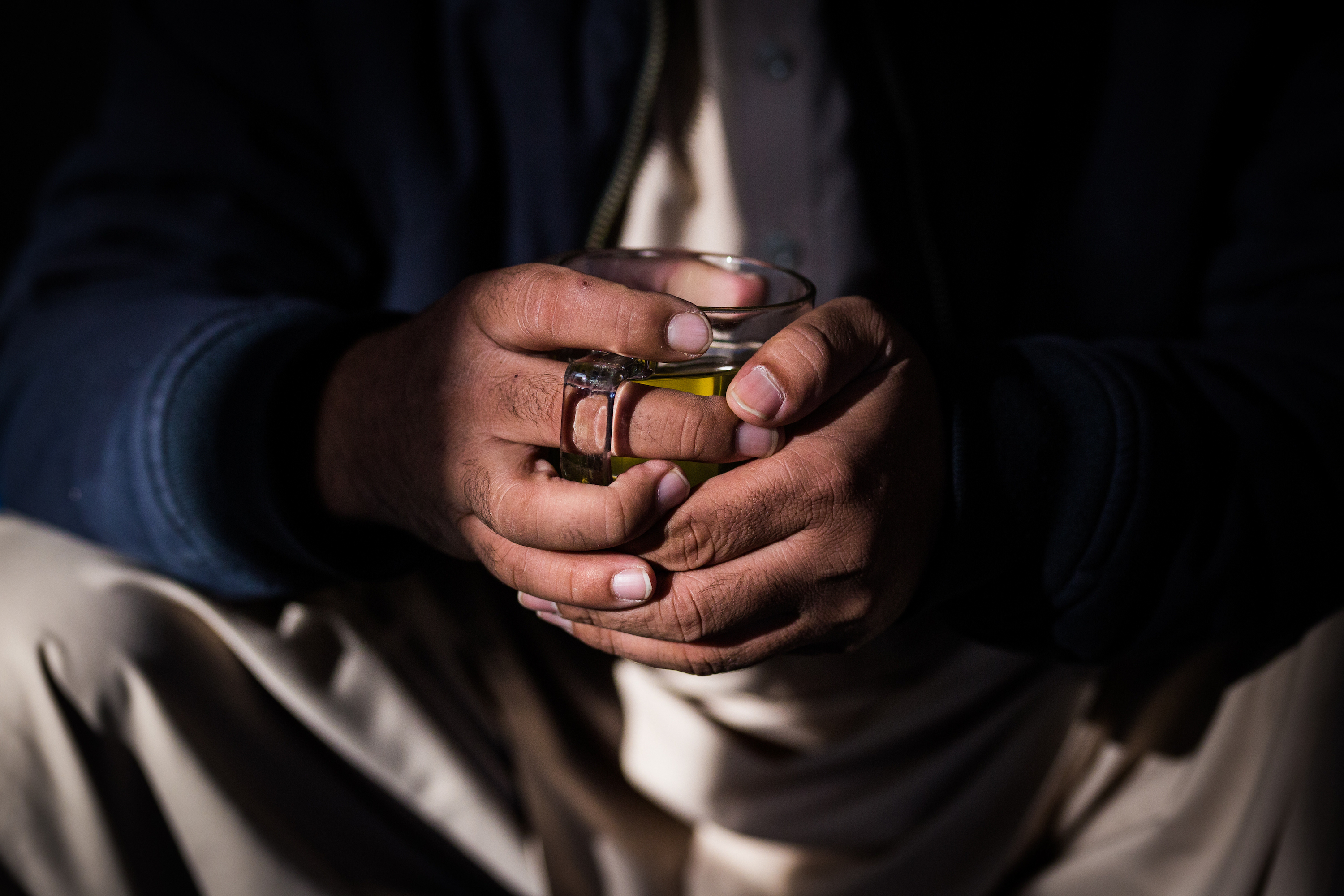 Hands around a cup of tea at a Kabul cafe
