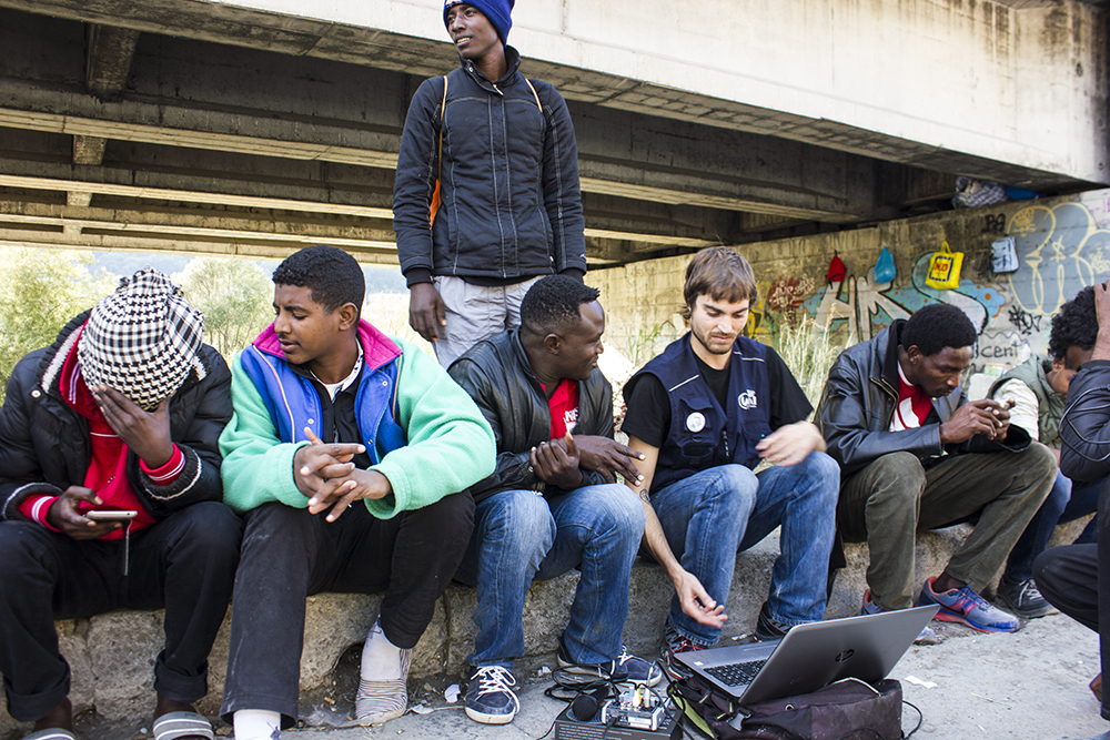 Asylum seekers and a volunteer sit outside around a laptop and equipment