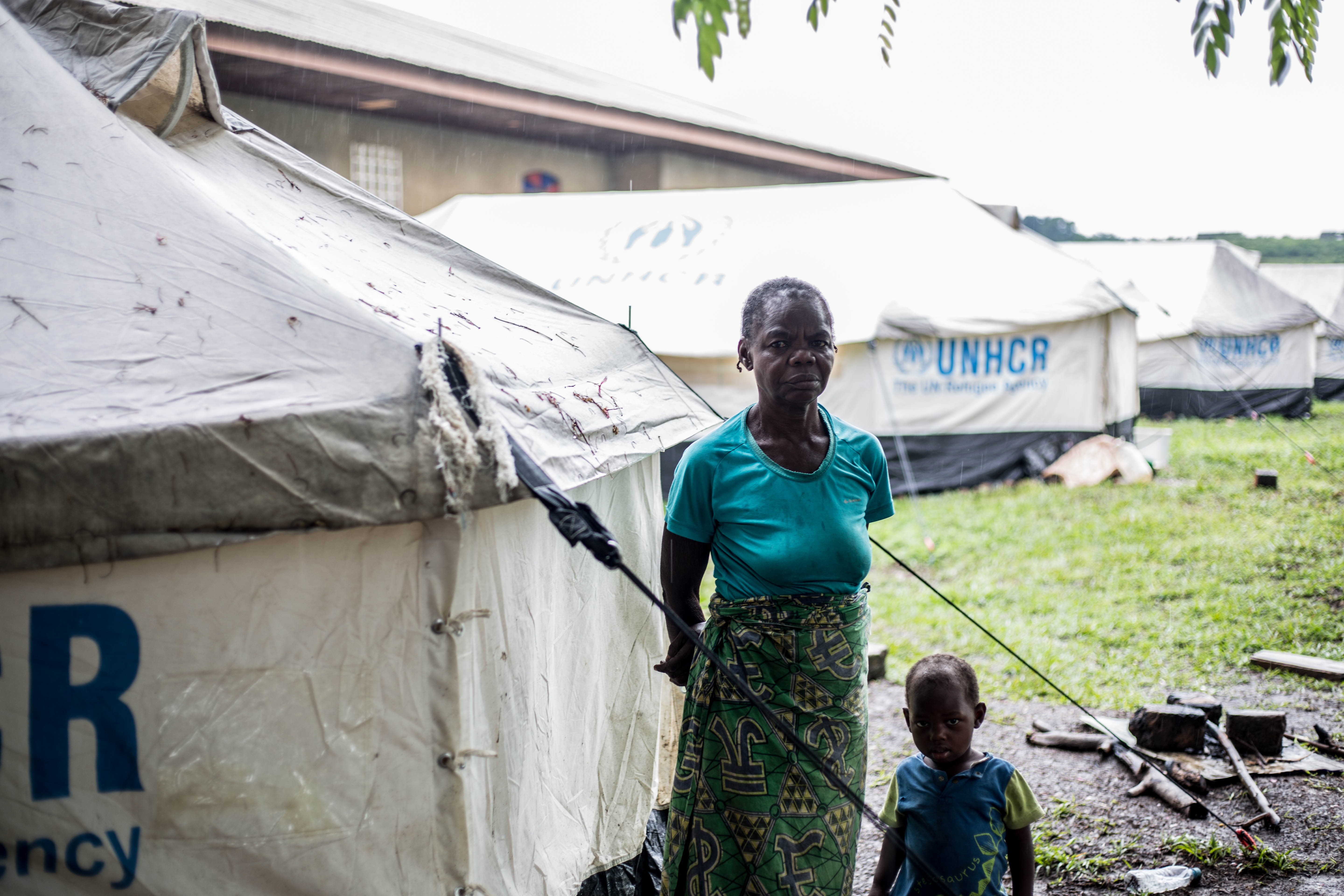 A woman and a child stand in front of a UNHCR tent in the rain facing the camera