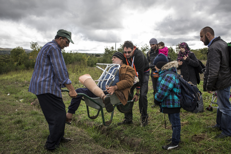 Disabled man carried over the bumpy ground to the border