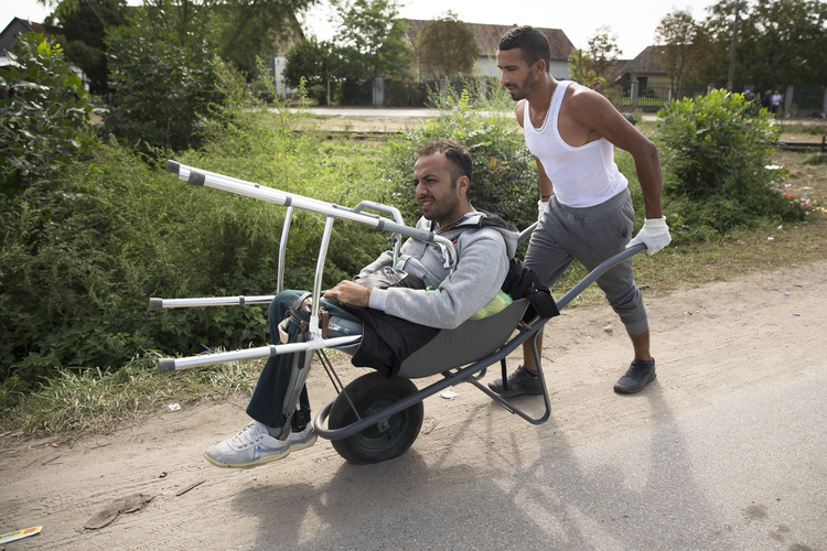 A man pushes his friend, who lost both his legs when ISIS attacked his university in Aleppo