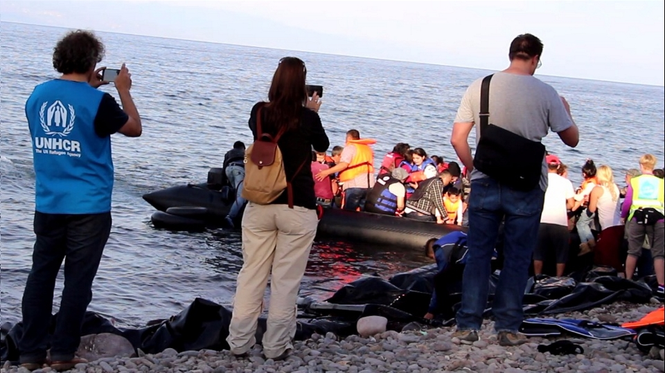 International aid workers take pictures as volunteers help arriving refugees from the boat