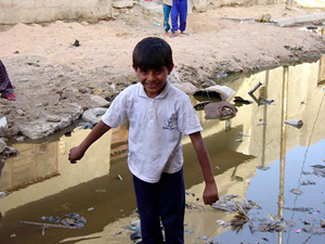 [Iraq] Young boy stands on the edge of sewage outflow.