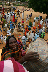 [Sudan] IDP women load their belongings onto trucks to move to another camp in Darfur.