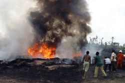[Nigeria] Local village youths try to put off the fire from the shell petroleum development company SPDC ruptured pipeline which exploded destroying farmlands and polluting fishing ponds in Rukpokwu near Port Harcourt Nigeria.