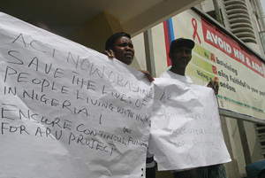 [Nigeria] Mary Ashie left, and Mohammed Farouk both people living with HIV/AIDS holds up placards as they protest outside the AIDS Alliance Nigeria office in Lagos.