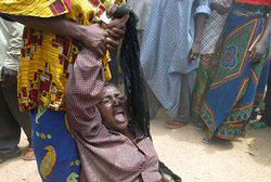 [Nigeria] A woman who lost her sister to the crisis cries at the police command centre for refugees in Kano.