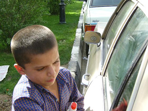 [Iran] Afghan street kid busy cleaning cars in Tehran.