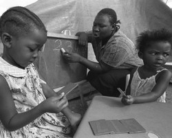 [Botswana] Two girls learn to count in a kindergarten class at a center for orphaned children in Francistown, Botswana.