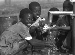 [Zambia] At a community school in Nthombimbi, Zambia, children gather around a water pump. The school is staffed and maintained by the community for children who cannot afford to attend formal school. Many of the pupils are orphans.