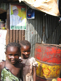 [Guinea] Girls in a Conakry shantytown in front of an election poster of President Lansana Conte.