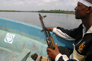 [Nigeria] An Ijaw militant loyal to Dokubo Asari, sits with his gun aboard a boat in the Niger Delta at Tombia, near Port Harcourt, in July 2004.