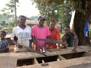 [Liberia] Prince Obi (in pink) struggles to earn his living as a carpenter in Zwedru. July 2004.