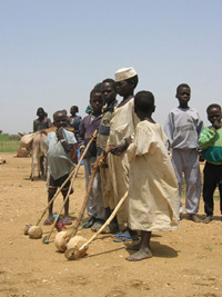 [Chad] Refugee children show off their home-made cars in Bredjing camp, eastern Chad. September 2004.