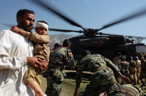 [Pakistan] Muzaffarabad, Pakistan, A father carries his injured son from a German SAR helicopter after they where taken from their devastated village. [Date picture taken: 10/13/2005]