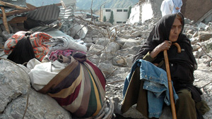 [Pakistan] Muzaffarabad, Pakistan, An elderly woman sits among the rubble, she received donated blankets and a jacket. She still has no place to go, her home completely destroyed. [Date picture taken: 10/15/2005]