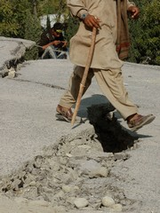 [Pakistan] Muzaffarabad, Pakistan, Pedestrians step of a crevasse in the pavement. The quake has left roads destroyed and impassable and often blocked by landslides making relief efforts difficult. Of the nearly 1000 villages affected by the quake interna