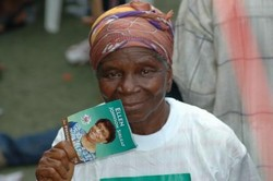 [Liberia] Liberian women have high hopes in this election, with a female frontrunner and women accounting for just over half of the 1.35 million registered voters. An old woman shows her colours at a rally in downtown Monrovia. 6th October 2005.