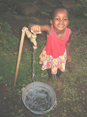 [Swaziland] Swazi girl drawing water from a community tap.