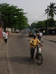 [Benin] A motorcycle taxi plies for trade on the streets of Cotonou.