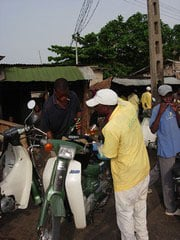[Benin] Motorcycle taxi drivers filling their tanks with contraband petrol from Nigeria at a roadside stall in Cotonou, Benin, April 2005.