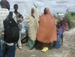 [Kenya] Displaced Somalis talking to a local official outside their shelter in the Kenyan border town of El Wak on 22 July 2005.