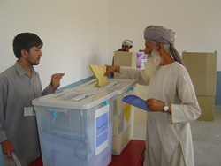 [Afghanistan] A voter in the northern city of Mazar-e-Sharif places her ballot paper in the box. Parliamentary and provincial polls took place in relative peace on Sunday, 18 September.