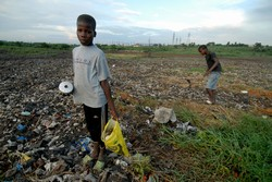[Ivory Coast] Two boys search for anything usable in a dumpsite, Abidjan, Ivory Coast, 25 September 2006. Residents have complained of symptoms they feared were linked to the dumping of 528,000 litres of liquid toxic waste. Many people are also seeking me
