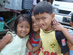[Indonesia] Children outside their barracks-style home outside tsunami-devastated Banda Aceh attempt a smile for the camera. More than 130,000 people were killed and over half a million left homeless in the 26 December 2004 disaster [Date picture taken: 1