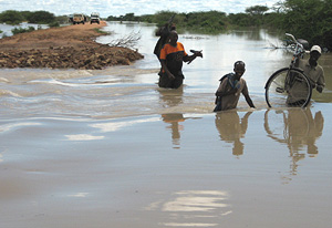 [Kenya] Men wade through water at Dadaab, 80 km from the Somali border, Kenya, 20 November 2006. The United Nations food agency has launched a series of airlifts and food drops for more than one million people hit by floods in Somalia and Kenya.