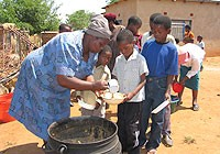 [Swaziland] A care giver serves lunch to children at a UNICEF-supported neighbourhood care point.